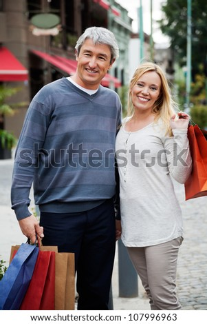 Portrait of a couple with shopping bags standing outdoors - stock photo