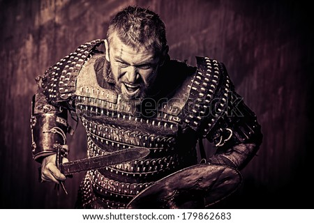 Portrait of a courageous ancient warrior in armor with sword and shield. - stock photo