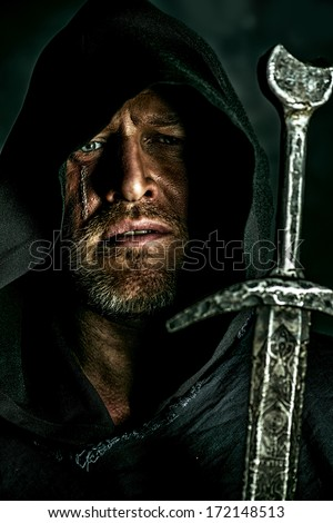 Portrait of a courageous warrior wanderer in a black cloak and sword in hand. Historical fantasy. - stock photo