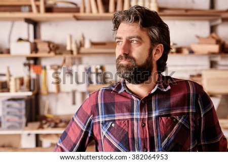 Portrait of a craftsman and owner of an artisan carpentry business in his workshop, looking away from the camera towards the light with a serious and confident expression. - stock photo