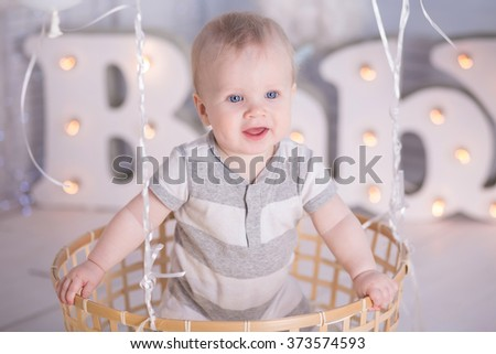 Portrait of a crawling baby on the decorative basket with balloons - stock photo