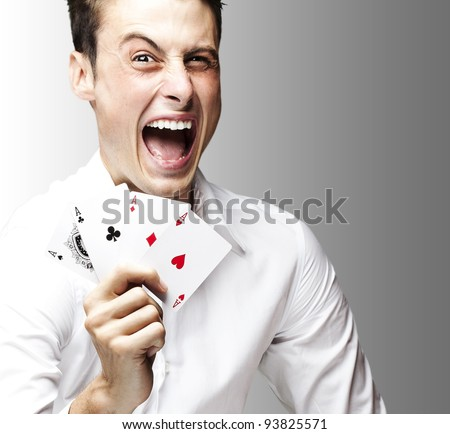 portrait of a crazy man showing poker cards against a grey background - stock photo