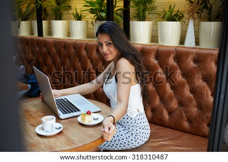 Portrait of a creative young woman work on laptop computer during breakfast in coffee shop, charming female freelancer sitting with open net-book in restaurant with cute smiling looking at the camera  - stock photo