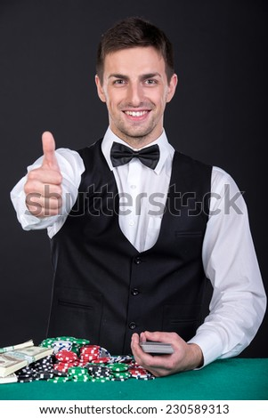 Portrait of a croupier with gambling chips on the green table and playing cards. - stock photo