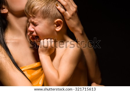 Portrait of a crying child on the mother's arms - stock photo