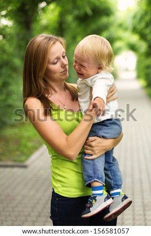 Portrait of a crying little boy who is being held by her mother , outdoors - stock photo
