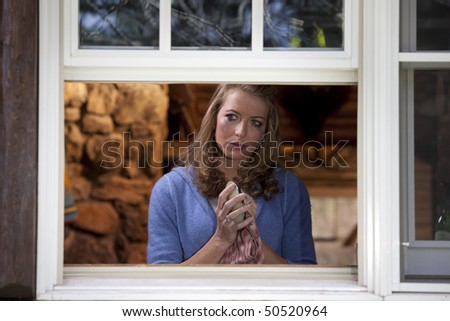 Portrait of a crying woman standing at her kitchen window and drying a dish. She is viewed from outside the window and is staring into the distance as mascara runs down her face. Horizontal format. - stock photo