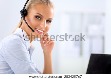 portrait of a customer service agent sitting at office - stock photo