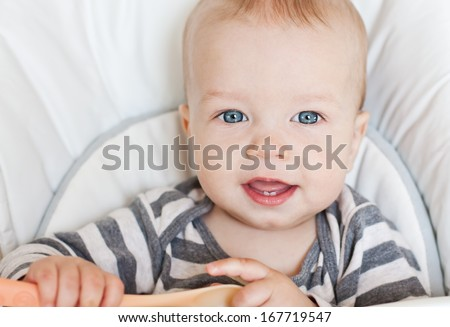 portrait of a cute baby boy smiling sitting at the table looking at the camera - stock photo