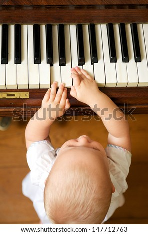 Portrait of a cute baby playing piano - from above - stock photo