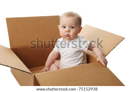 Portrait of a cute baby sitting in a brown cardboard box - stock photo