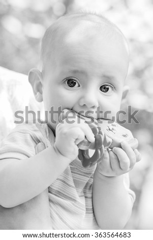 portrait of a cute baby sucks rattle outdoors  ( black and white ) - stock photo