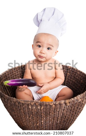 Portrait of a cute baby wearing a chef hat with healthy fruit, isolated on white - stock photo