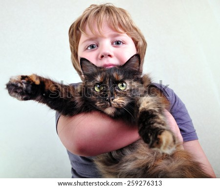 portrait of a cute blond boy with a cat - stock photo
