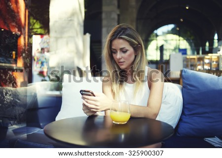 Portrait of a cute blonde female read something on her smart phone while sitting in modern coffee shop, beautiful young hipster girl using cell telephone while enjoying her free time in expensive cafe - stock photo
