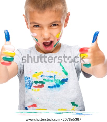 Portrait of a cute boy playing with paints and showing thumb up sign using both hands, isolated over white - stock photo
