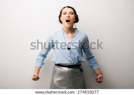 portrait of a cute brunette girl rejoices victory with clenched fists - stock photo
