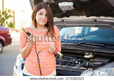 Portrait of a cute brunette holding jumper cables and asking for help with her car - stock photo