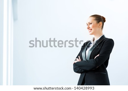 Portrait of a cute business woman stands with his arms crossed - stock photo