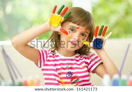 Portrait of a cute cheerful girl showing her hands painted in bright colors - stock photo