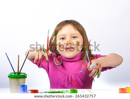 Portrait of a cute cheerful girl showing her hands painted in bright colors, on a white background - stock photo