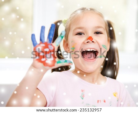 Portrait of a cute cheerful girl showing her hands painted in bright colors, over snowy background - stock photo
