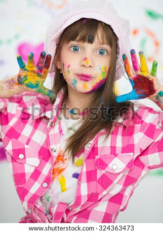 Portrait of a cute cheerful happy little girl showing her hands painted in bright colors - stock photo