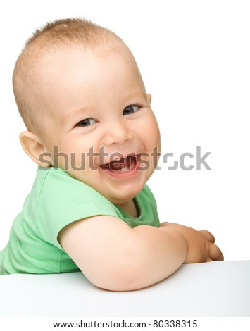 Portrait of a cute cheerful little boy, who is smiling while sitting at table, isolated over white - stock photo