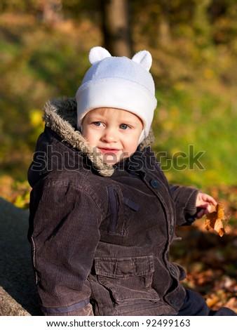 Portrait of a cute child in white cap. Autumn nature background - stock photo