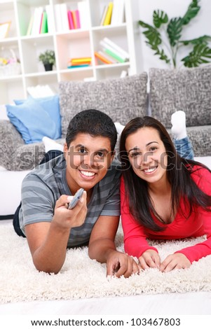 Portrait of a cute couple watching TV in their living room - stock photo