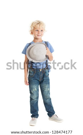 Portrait of a cute curly blond boy wearing a blue shirt and jeans in full growth. Boy holding a hat. Studio shot, isolated on white background. - stock photo