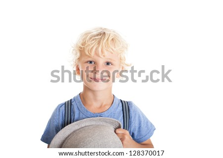 Portrait of a cute curly blond boy wearing a blue shirt, suspenders and hat. Boy smiling and holding a hat. Studio shot, isolated on white background. - stock photo