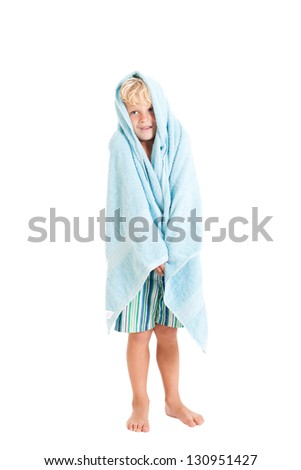 Portrait of a cute curly blond European boy in a towel and swimming shorts. Studio shot, isolated on white background. - stock photo