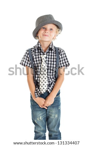 Portrait of a cute curly blond European boy wearing a plaid shirt, tie, suspenders and hat. Studio shot, isolated on white background. - stock photo