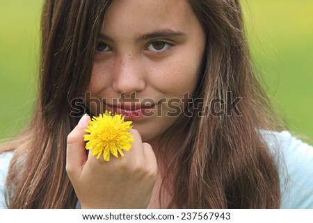 Portrait of a cute eleven year old with dandelion flower. - stock photo