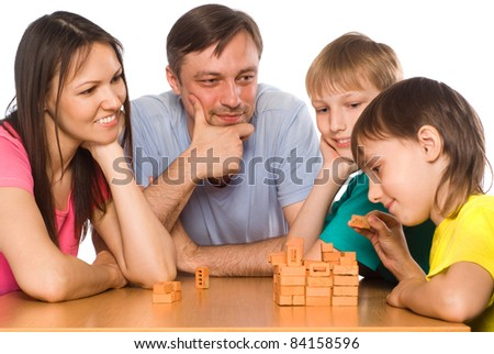 portrait of a cute family playing at table - stock photo