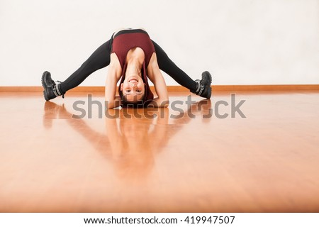 Portrait of a cute female flexible dancer having fun in a dance studio and arching her back while doing a headstand - stock photo