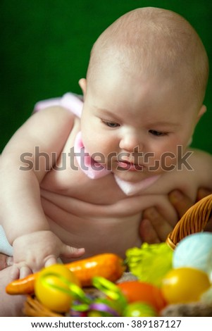 Portrait of a cute funny baby with an easter basket of eggs - stock photo