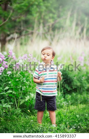 Portrait of a cute funny little boy toddler standing in the forest field meadow with dandelion flowers in hands and blowing them on a bright summer day, summer fun, lens flare from above - stock photo