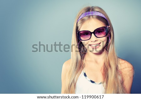 Portrait of a cute girl in sunglasses posing at studio. - stock photo
