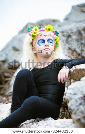 Portrait of a cute girl outdoors with sugar skull makeup - stock photo
