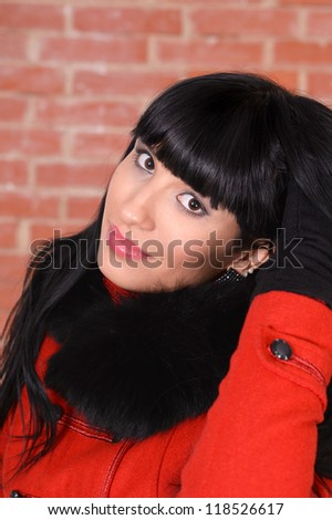 portrait of a cute girl posing against a brick wall - stock photo