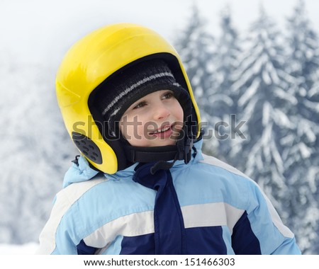 Portrait of a cute happy child skier, boy or girl, with yellow skiing helmet in a winter ski resort. - stock photo