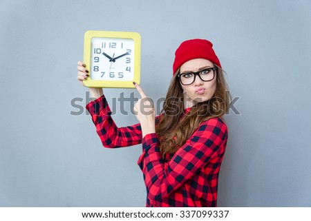 Portrait of a cute hipster woman pointing finger on wall clock over gray background - stock photo