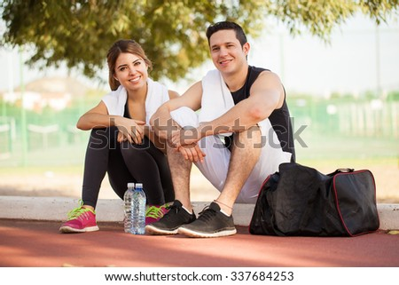 Portrait of a cute Hispanic couple resting after working out together outdoors and smiling - stock photo