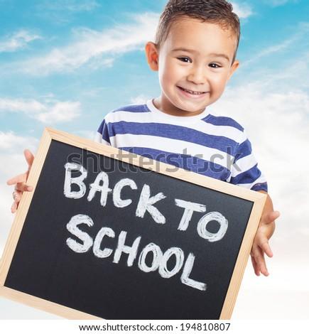 portrait of a cute kid holding a chalkboard - stock photo