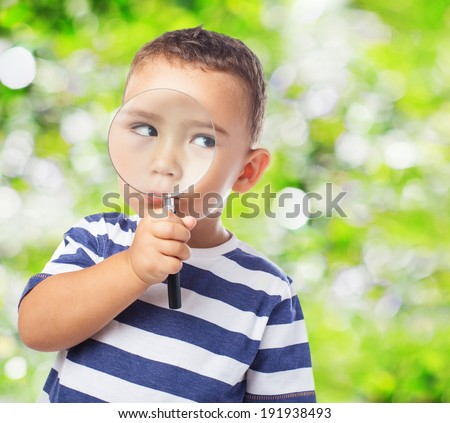 portrait of a cute kid looking through a magnifying glass - stock photo