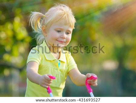Portrait of a cute little baby girl walking with pram outdoors, happy child with toys playing in the park on a bright sunny day, preschoolers daycare - stock photo