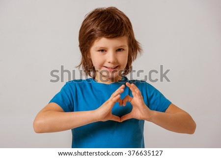 Portrait of a cute little boy in a blue t-shirt  showing a heart with his hands, looking in camera and smiling while standing on a gray background - stock photo