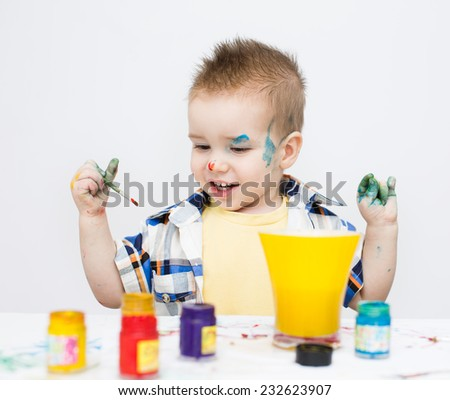 Portrait of a cute little boy playing with paints - stock photo